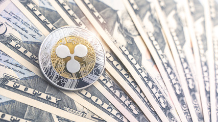 Physical version of Ripple and dollar banknotes. Exchange xrp for a dollar symbol. Conceptual image for worldwide cryptocurrency and digital payment system.