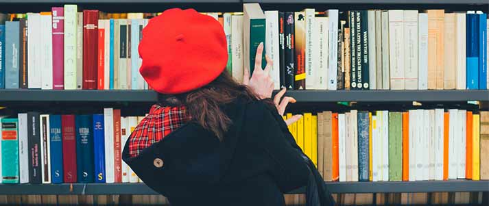 woman looking through books on shelves
