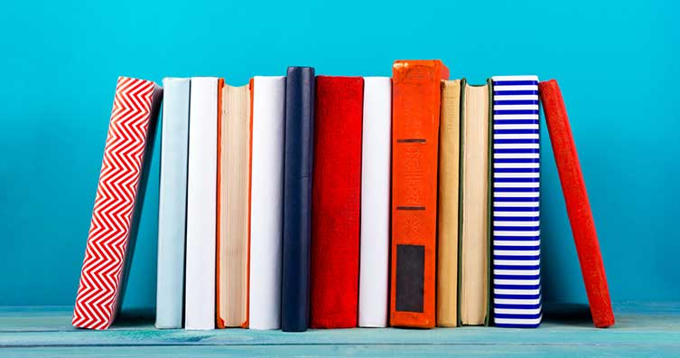 colourful books stacked against blue background
