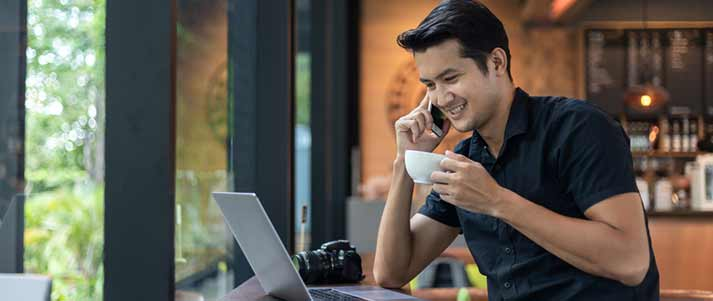 man working on phone in cafe