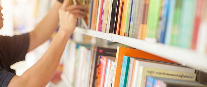 man taking book off shelf in library