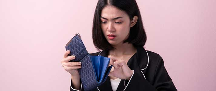 woman looking in purse frowning