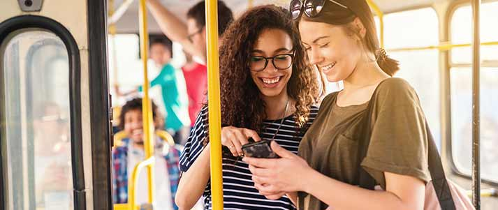 Two friends on a bus looking at phone