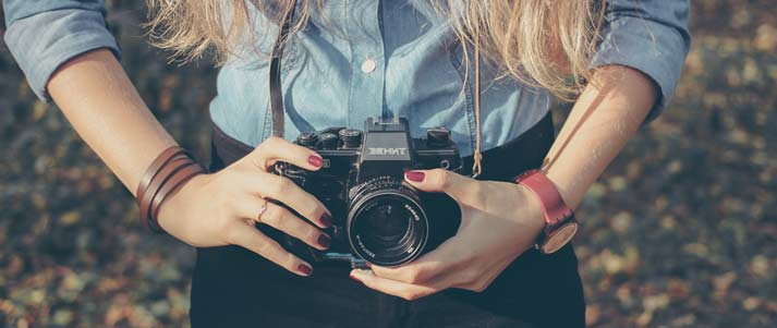 woman holding camera in front of her waist