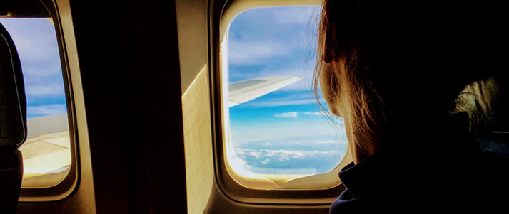 person looking out of plane window