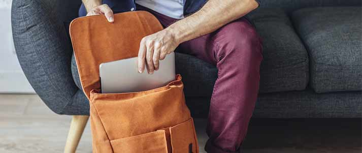 person packing laptop in bag